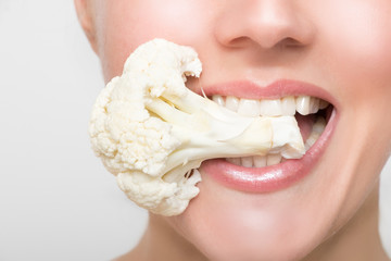 Woman's mouth with cauliflower between her big white teeth
