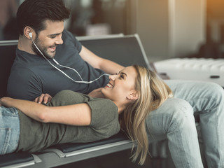 Outgoing male telling with laughing girlfriend while hearing song with earphones. Happy couple concept