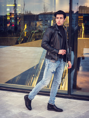 One handsome young man in urban setting in modern city, walking, wearing black leather jacket and jeans