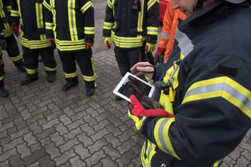 Feuerwehrmann hält ein Tablet in der Hand
