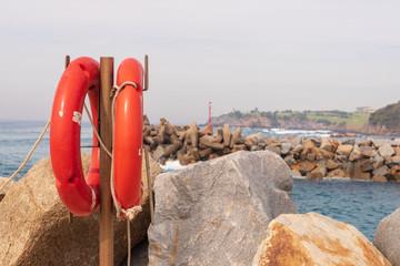 Orange lifebuoys at harbour entrance at Narooma, NSW, Australia