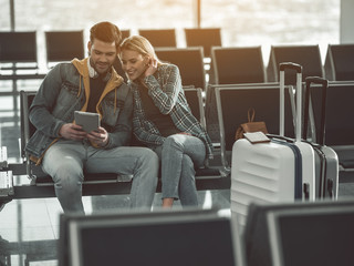 Portrait of cheerful man speaking with happy female. They looking at digital device while locating in airport