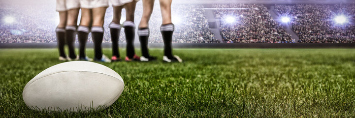 Digital image of crowded soccer stadium against rugby players standing together before match