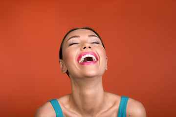 Portrait of nice girl with cared face smiling at the top of her voice. Isolated on background