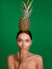 Portrait of bare girl with dazed face holding pine on head and covering mouth with hand. Isolated on background