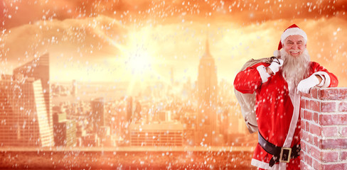 Portrait of Santa Claus carrying bag full of gifts against sun shining over city