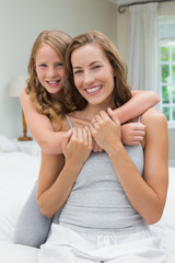 Happy girl embracing mother from behind in bedroom