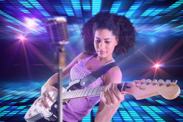 Pretty girl playing guitar against digitally generated cool disco design