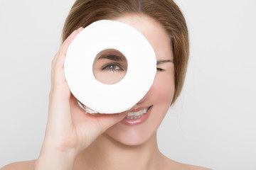Beautiful woman looks through a roll of toilet paper