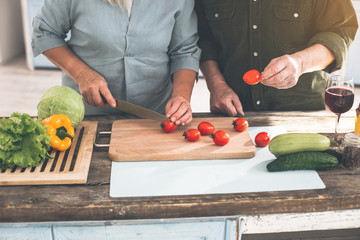 Close up of mature couple hands cooking together healthy dinner. Woman is cutting vegetables by knife while man is holding tomato