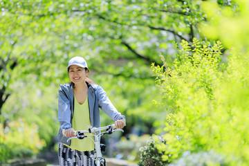 ロードバイクを押しながら散歩する女性