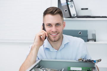 Portrait of smiling computer engineer on call in front of open cpu