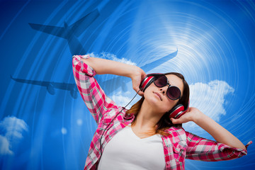 Casual brunette listening to music against bright blue sky with clouds