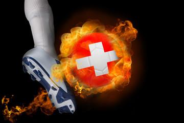 Football player kicking flaming switzerland ball against black