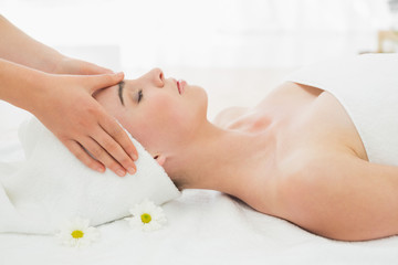 Hands massaging womans face at beauty spa