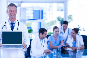 Doctor showing laptop with colleagues behind