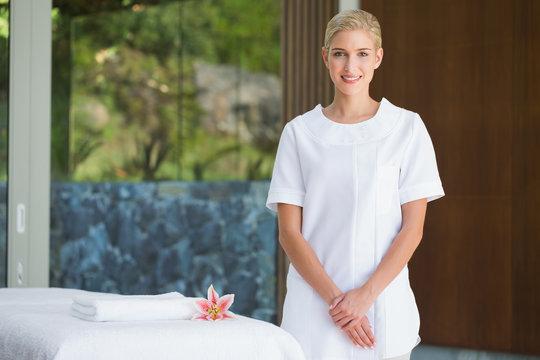 Smiling beauty therapist standing beside massage towel