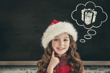 Cute girl in santa hat against blackboard on wall