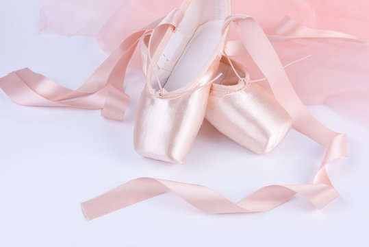 Closeup of ballet shoes with pink ballet costume
