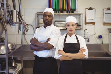 Two chefs standing with arms crossed in the commercial kitchen