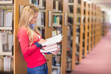 Mature student picking out book in library