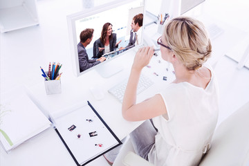 Female photo editor working on computer against attractive businesswoman laughing with her team