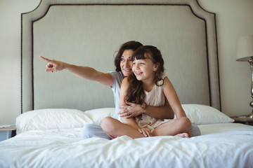 Mother with daughter pointing at a distance on bed