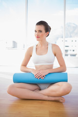 Thinking fit brown haired model in sportswear sitting and carrying an exercising mat
