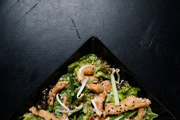 homemade traditional oriental meal. food cooking. fried squid and vegetable salad on dark background. copy space concept