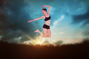 Full length of a sporty young woman jumping against blue sky over grass