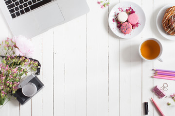 Horizontal flat top view of white desk with open metal laptop, decorated with flowers, surrounded with pastry, tea cup and stationery for creative work, free space in centre for advertisement