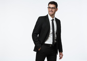 Indoor photo of young European Caucasian male in formal clothes pictured isolated on white background looking backwards through glasses and moving as if hurrying to business meeting, smiling