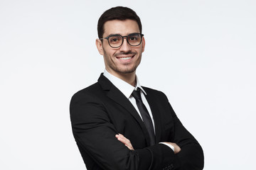 Horizontal photo of handsome Caucasian businessman isolated on white background wearing black suit, white shirt, tie and eyeglasses with arms crossed and positive face expression, ready to cooperate