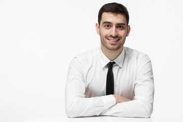 Indoor picture of handsome Caucasian male dressed in white shirt and necktie pictured isolated on white background resting arms on white table feeling optimistic and ready for business communication