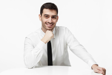 Horizontal portrait of young European businessman isolated on white background wearing formal clothes with tie leaning on white table, pressing fist to chin, looking interested in conversation