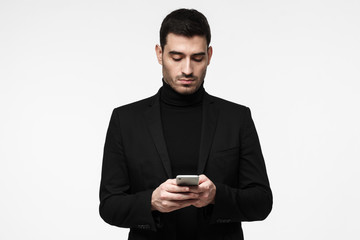 Indoor portrait of young European Caucasian male in black clothes isolated on white background holding cellphone in front of him, typing or browsing with concentrated face trying to find something out