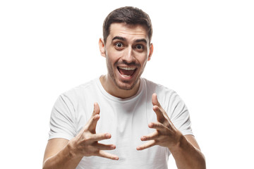 Horizontal portrait of young European male isolated on white background wearing casual T-shirt looking excited and spreading hands forward as if trying to catch luck or chance to get something great
