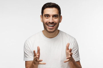 Closeup photo of handsome Caucasian man pictured isolated on grey background dressed in casual T-shirt pulling hands forward and smiling as if waiting for ball in game or profit he wants to get