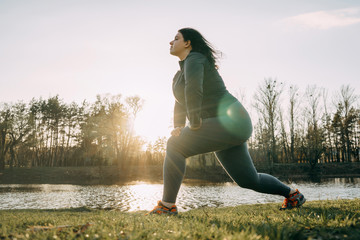 Overweight woman warming up before jogging