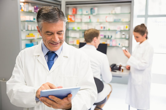 Senior pharmacist using tablet pc