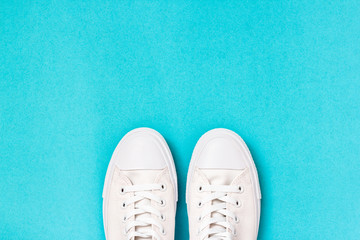 Pair of new white sneakers on blue background. Top view