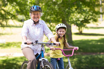 Happy grandmother with her granddaughter on their bike