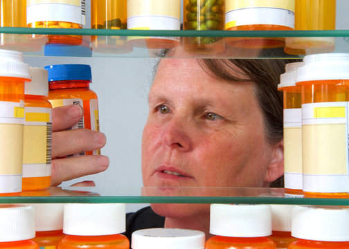 Middle aged caucasian woman reading medication label on prescription bottle in medicine cabinet, view from inside of med cabinet. Concept of wellness, overwhelming management of medications.
