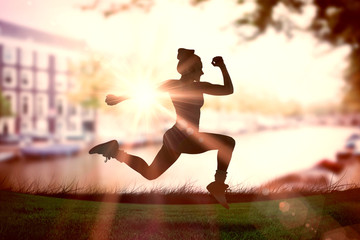 Fit brunette running and jumping against sun shining over park