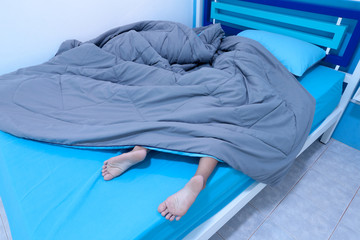 child sleep in bed with Legs sticking out from under the blanket in the bedroom