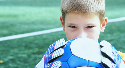 Portrait of teenage goal keeper holding ball on school soccer pitch