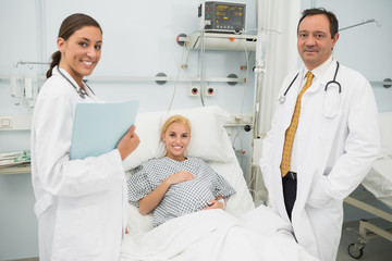 Female and male doctor standing next to a woman patient