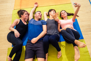 A cheerful group of people are photographed on the phone after classes on stretching in a yoga class on the floor