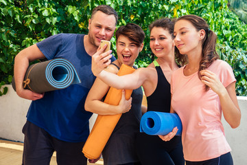 A cheerful group of people are photographed on the phone after stretching exercises in a yoga class