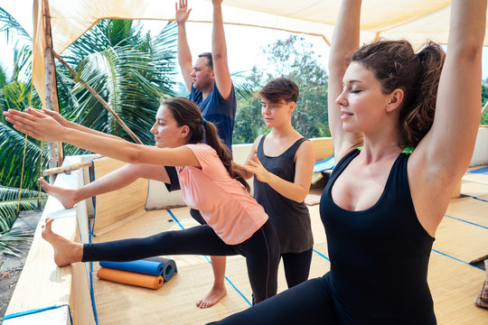 group stretching exercises in a yoga class together with an instructor